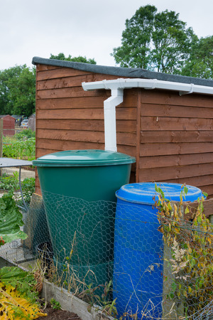 Water barrels attached to garden shed Stock Photo