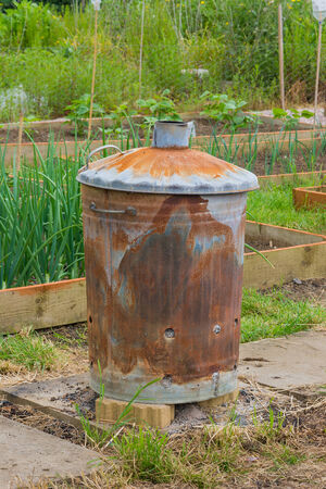 incinerator: Rusty garden incinerator with plants in background Stock Photo