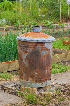 inceneritore: Rusty inceneritore giardino con piante in background Archivio Fotografico