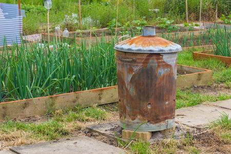 incinerator: Rusty garden incinerator with plants in background Stock Photo