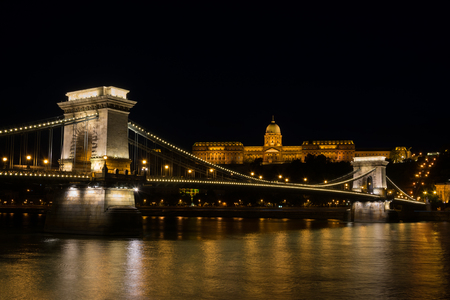 Chain bridge Budapest Hungary illuminated at night with old palace Stock Photo