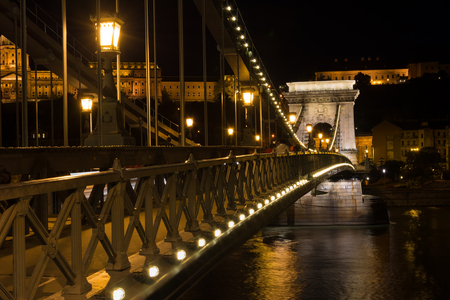 Chain bridge Budapest Hungary illuminated at night with old palace in the background Stock Photo