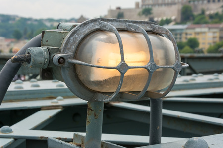 Metal encased glowing lamp attached to bridge railing
