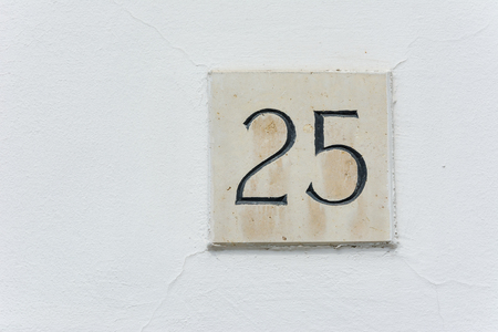 House number twenty five on a stone plaque with a green wall