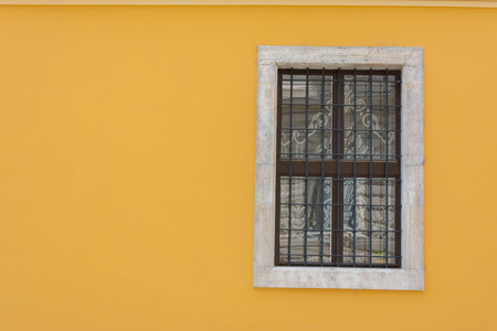 Yellow wall with wrought iron window Stock Photo