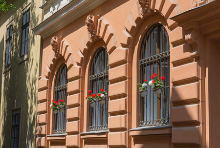 Ornate wrought iron window shutters with germanium plants and terracotta wall Stock Photo