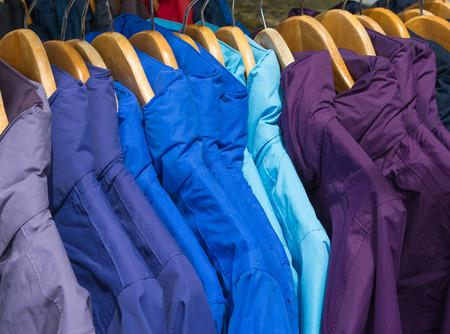 rainwear: Rainproof jackets in bright colors on a rack for sale.