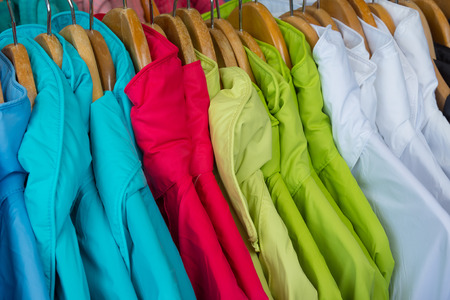 outer clothing: Rainproof jackets in bright colors on a rack for sale.
