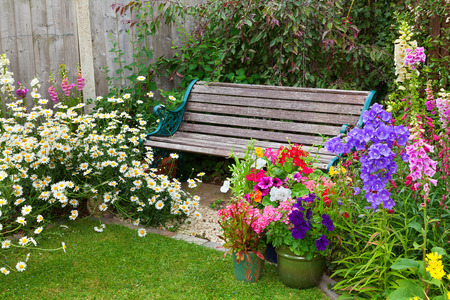 Cottage garden with wooden bench and flowers in containers. Banco de Imagens - 41676933