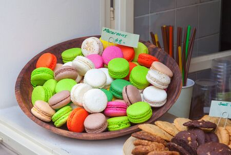 window display: Bowl of colorful macaroons on display in a shop window Stock Photo