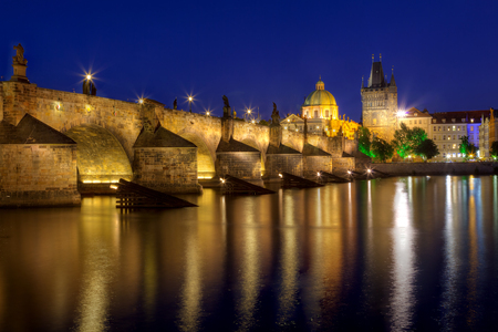 francis: View at night across the Vltava River in Prague with Charles Bridge St Francis Church Stock Photo