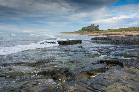 Bamburgh castle viewed from a distance at dusk along the coast England Stock Photo