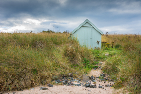 Lonely beach hut with footpath leading to it from the beach under stormy sky