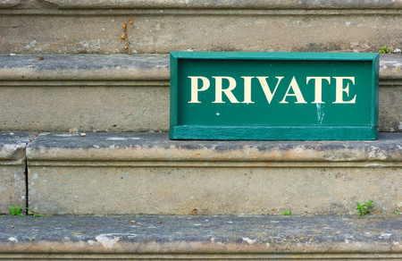 Old Private sign standing on weathered stone steps Stock Photo