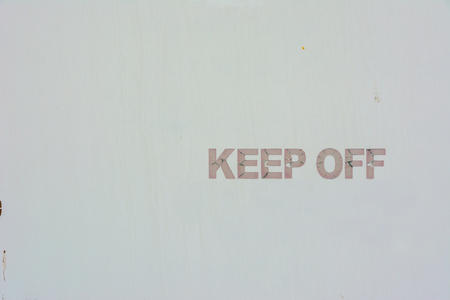Keep Off hand painted sign against a plain white metal background Stock Photo