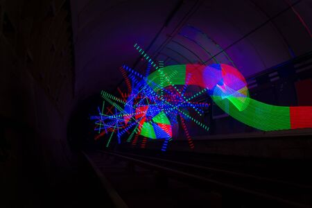 Multi-colored LED light used to create a pattern in a dark tunnel Stock Photo