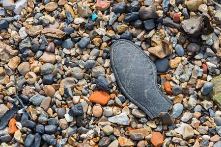 Discarded remains of a shoe on a pebble beach Banco de Imagens
