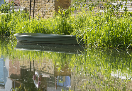 Tranquil river scene with empty rowing boat moored at the bank. Banco de Imagens - 102076172