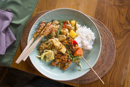 Plate of typical Balinese, Thai, Indonesian food with chicken satay sticks, rice, deep fried tempeh, steamed tuna,coconut and snake bean salad, vegetables in peanut sauce and chicken coconut curry.