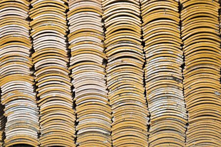 Stacks of yellow ceramic glazed curved roof tiles in a symmetrical pattern. Reklamní fotografie