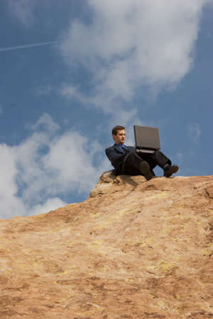 Man sitting on a hilltop conducting business Stock Photo