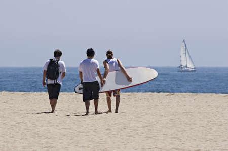 compa�erismo: Tres hombres j�venes caminando en la playa