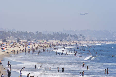 congregate: Jet flying over a crowded beach