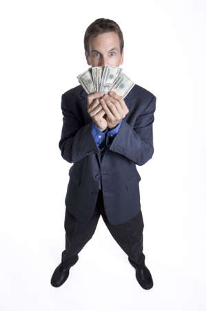 corporate greed: Businessman holding money up to his face