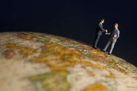 Business figurines on earth globe shaking hands
