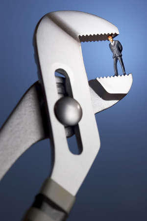 devise: Business figurines in a clamp Stock Photo