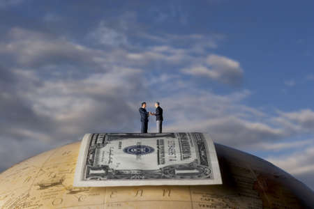Business figurine placed on globe with money Banco de Imagens