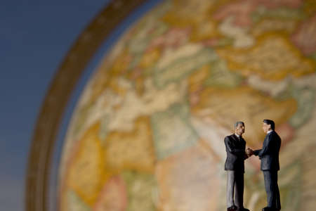 Business figurine placed on or next to an antique earth globe.