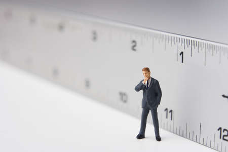 Business figure placed next to a ruler