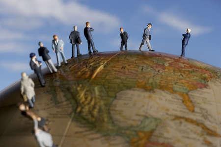 Business figurine placed on antique earth globe. Banco de Imagens