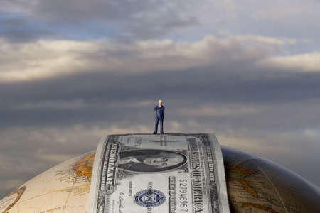taxman: Business figurine placed on earth globe with money Stock Photo