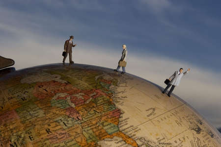 Business figurine placed on antique earth globe. Stock Photo