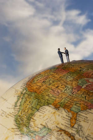 placed: Business figurine placed on antique earth globe. Stock Photo