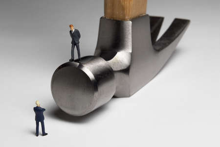 Building a business: Business figurines place with a hammer.
