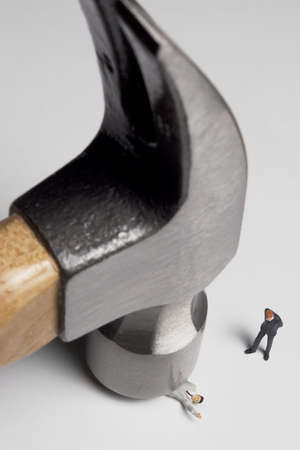 reasonable: Business figurines placed with a hammer. Stock Photo