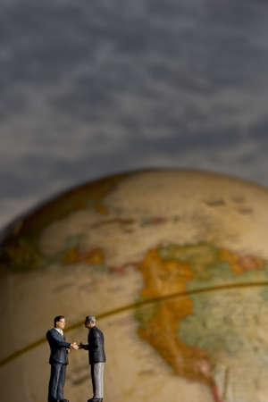 figurines: Business figurines and earth globe.