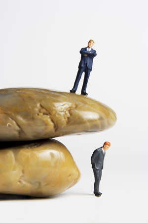 Business figurine placed next to rocks
