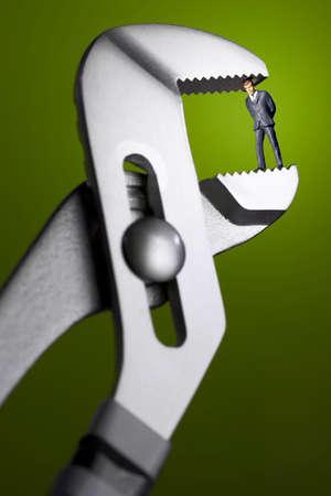Business figurine held in pliers