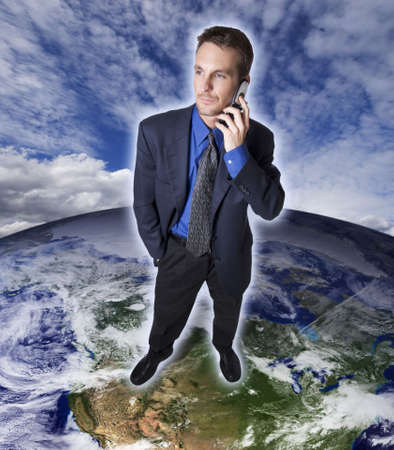 Businessman talking on a cellular phone standing on the earth. photo