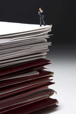 Business figures and stacks of papers and folders