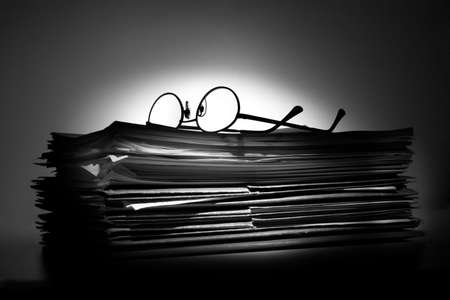 Glasses and stack of papers and folders photo