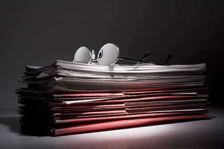 devise: Glasses and stack of papers and folders