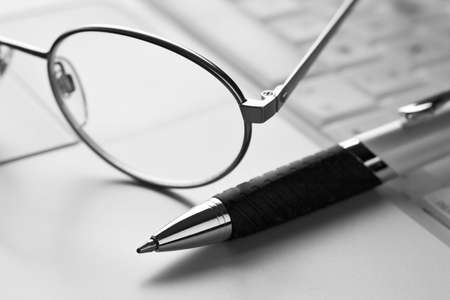 Glasses, pen and laptop