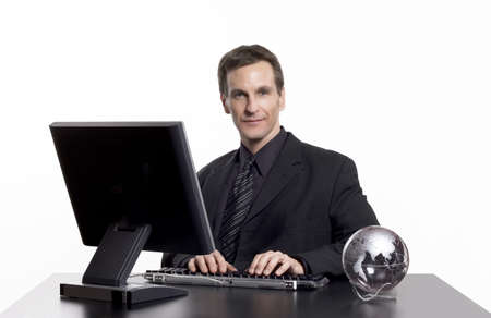 Businessman working on the computer, with an earth globe on his desk. Foto de archivo