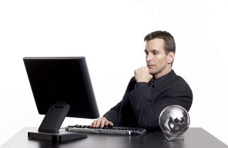 businessman working at his computer: Businessman working on the computer, with an earth globe on his desk. Stock Photo