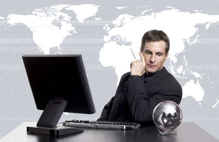 Businessman working at his desk looking at globe with world map in the background
